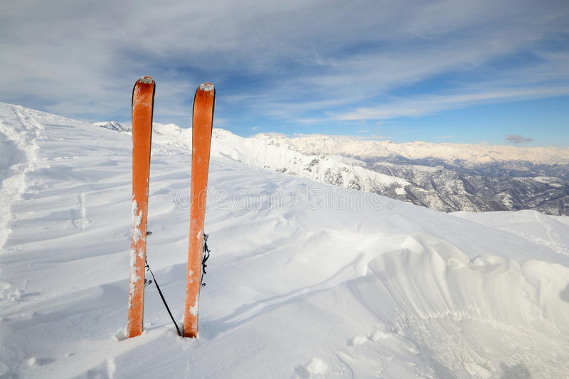 Ski touring exploration. Pair of back country ski with orange climbing skin or sealskin on the summit with superb view of the valleys below stock images