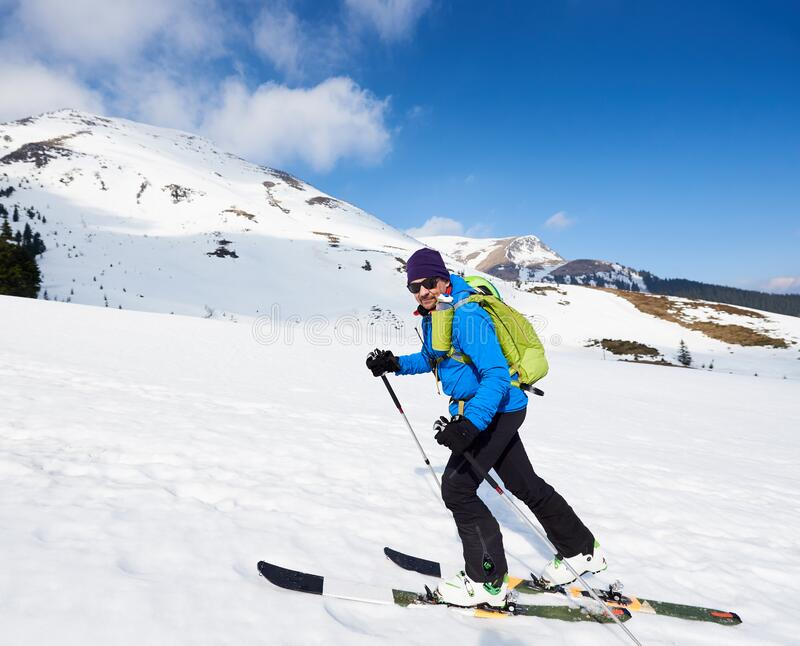 Ski touring man ascending during ski touring in the spectacularly white mountains. Snow and winter activities, skitouring in mountains royalty free stock photos