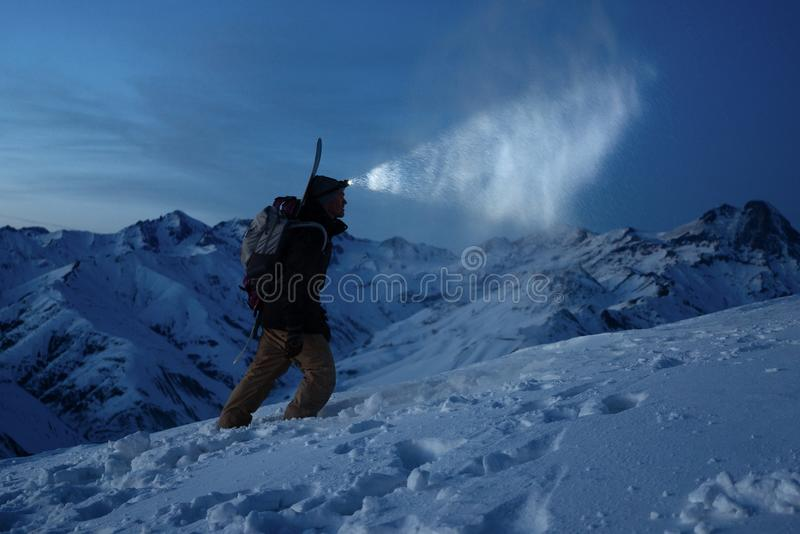 Ski touring man commit climb on night winter mountain. Tourist with headlamp, backpack and a snowboard behind his back walking on stock image