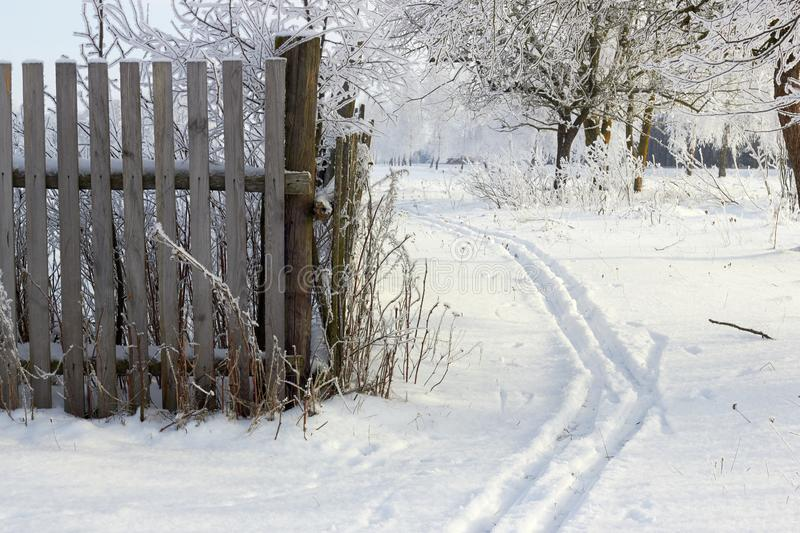 Ski track near rustic fence run into dreamy fabulous snowy winter landscape. With trees covered with snow on sunny morning. Beautiful season winter background royalty free stock photography