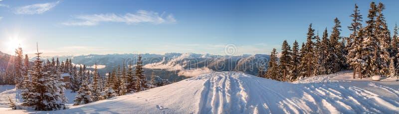 Ski tracks dropping off a ridge, looking out onto the mountains near Whistler, BC. Ski tracks dropping off a ridge, looking out onto the mountains near Whistler royalty free stock photos
