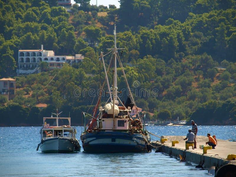 Skiathos, Griekenland - Vissers op het dok dichtbij de vissersboten royalty-vrije stock fotografie