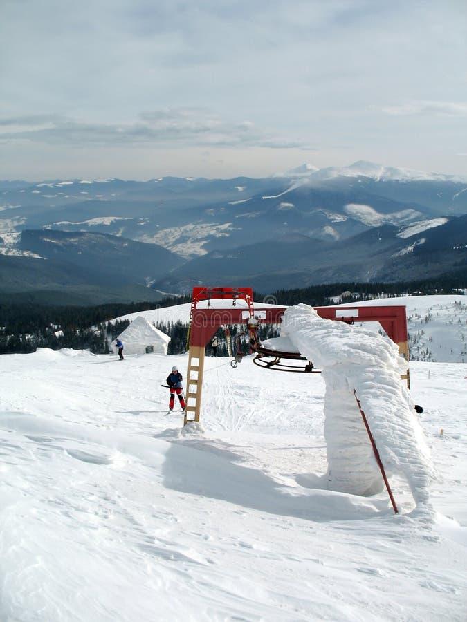Skiaufzug auf Schnee umfasste Bergspitzen auf Hoch lizenzfreie stockbilder