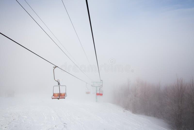 Skiaufzug mit den Sitzen, die über den Berg und die Wege von den Himmeln hinausgehen stockbilder
