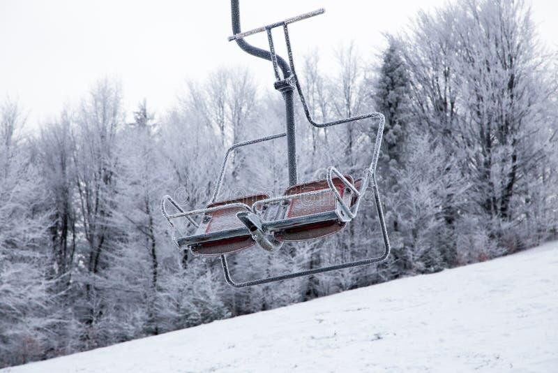 Skiaufzug mit den Sitzen, die über den Berg und die Wege von den Himmeln hinausgehen lizenzfreie stockbilder
