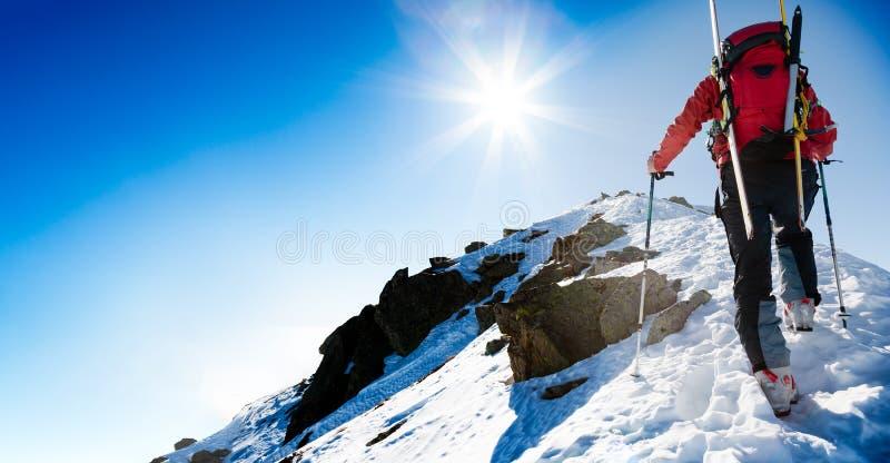 Skibergbeklimmer die langs een steile sneeuwrand met sk naar boven gaan royalty-vrije stock afbeelding