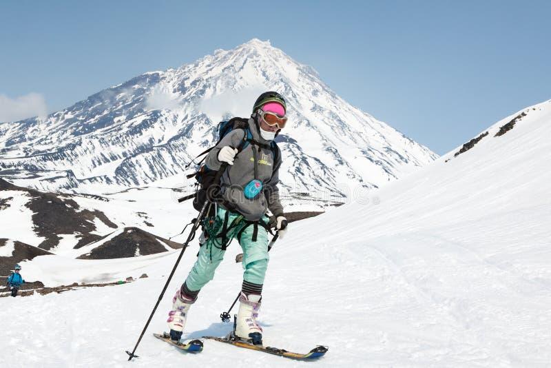 Skibergsteigeraufstieg der jungen Frau auf Berg auf Hintergrundvulkan stockbild