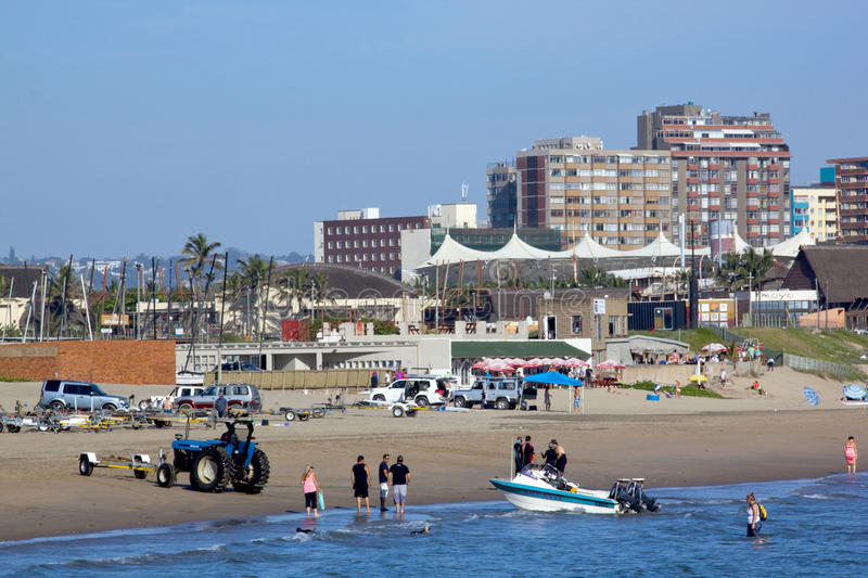 Skiboat Club and Beachfront in Durban South Africa. DURBAN, SOUTH AFRICA - FEBRUARY 16, 2014: Skiboat being pulled out of sea by tractor at skiboat club as many royalty free stock photos