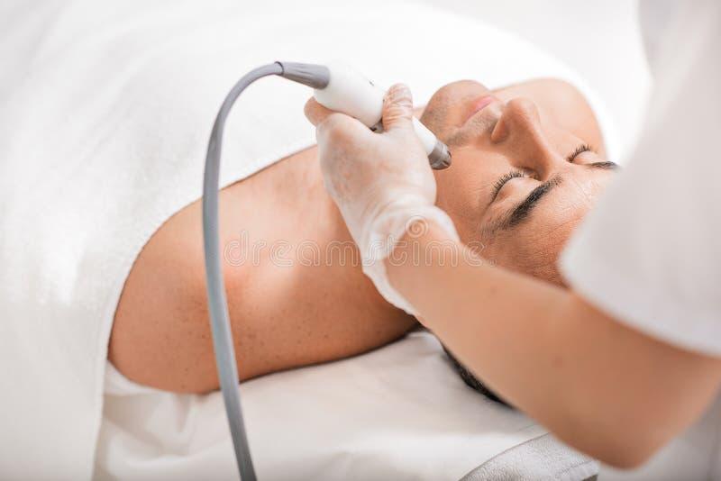 Skicklig cosmetologist som genomgår anti--åldras tillvägagångssätt för ultraljud arkivfoto