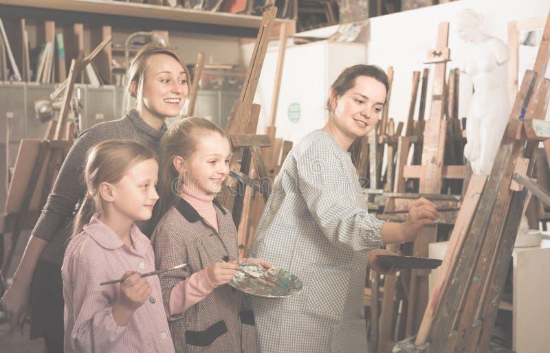Skicklig kvinnalärare som visar henne expertis under målninggrupp fotografering för bildbyråer