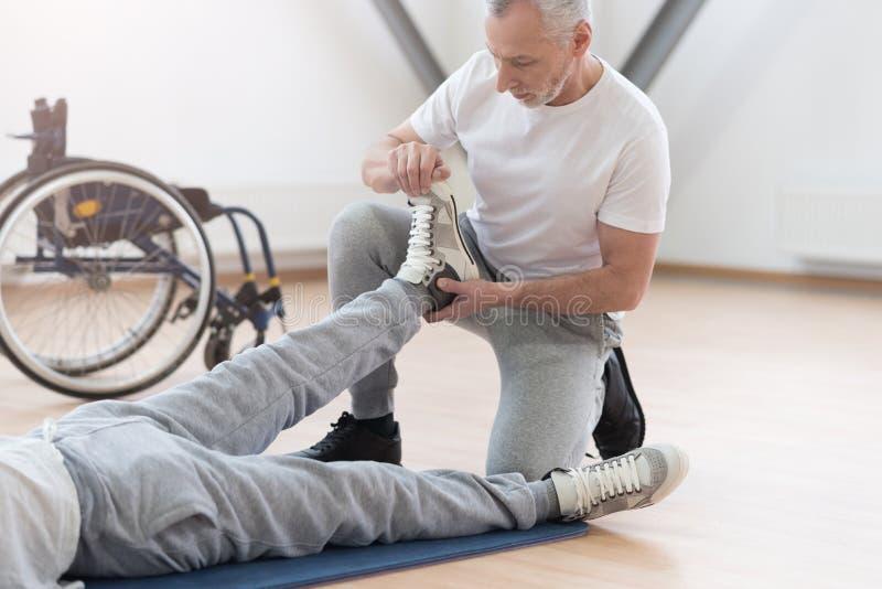Skicklig lagledare som sträcker lemmar av handikappade personer i idrottshallen fotografering för bildbyråer