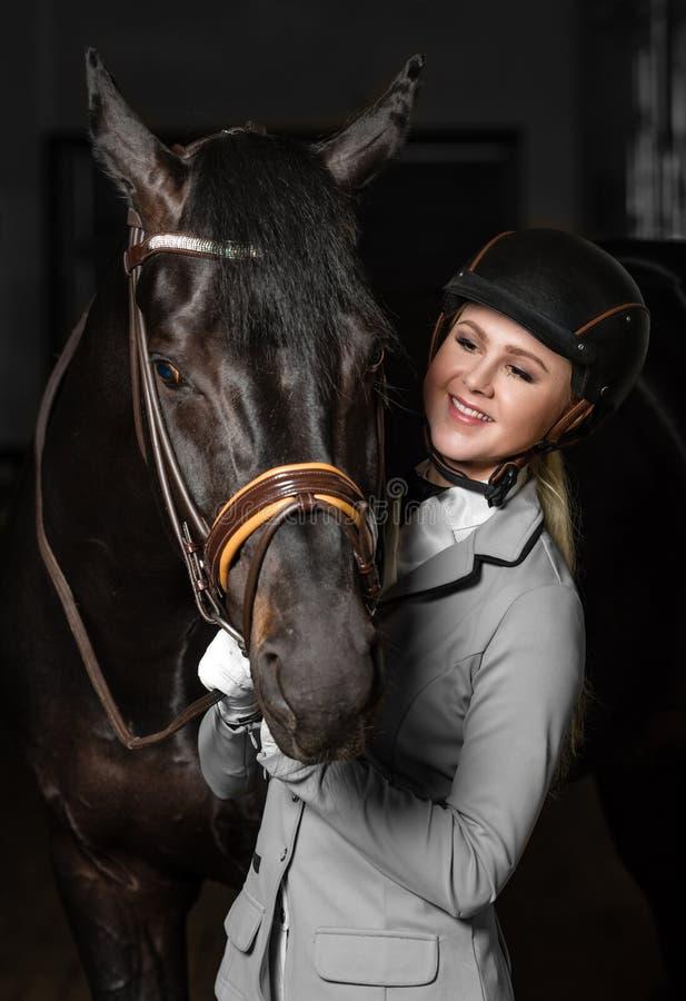 Skicklig ryttarinna i likformig med en brun häst i stallet royaltyfria bilder