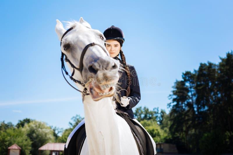 Skicklig ryttarinna med den bärande hjälmen för lång flätad tråd som rider hennes häst royaltyfria bilder