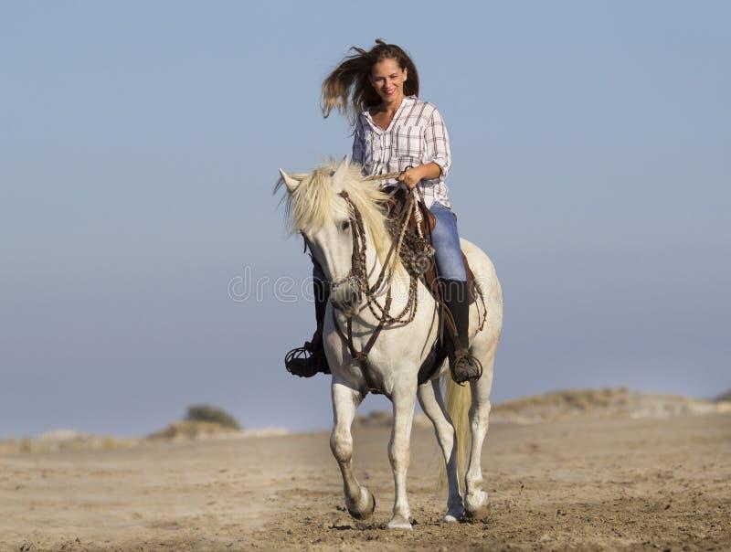 Skicklig ryttarinna på stranden royaltyfria bilder
