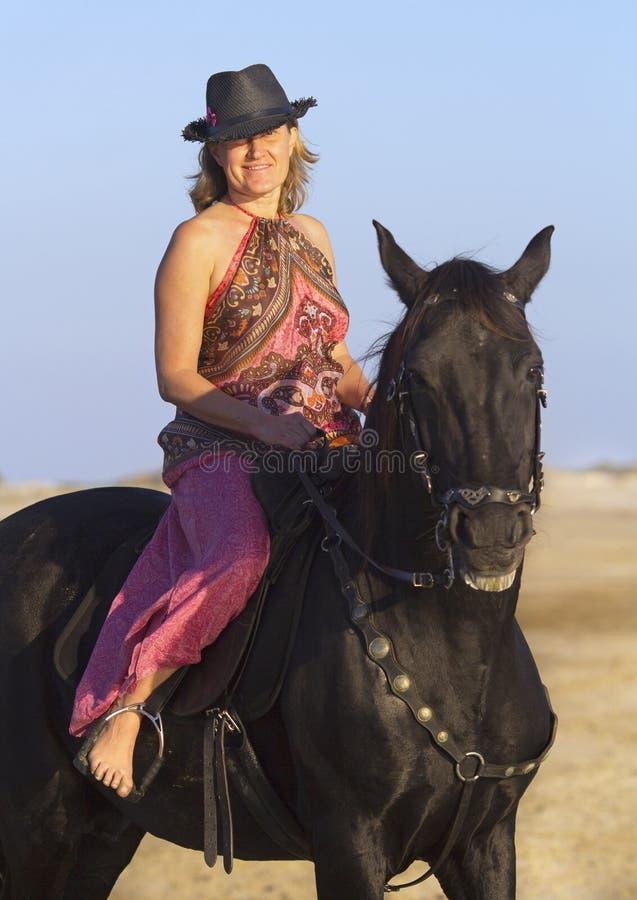Skicklig ryttarinna på stranden royaltyfri foto