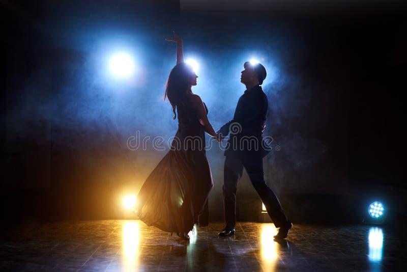 Skickliga dansare som utför i det mörka rummet under konserten, tänder och röker Sinnliga par som utför ett konstnärligt royaltyfria bilder