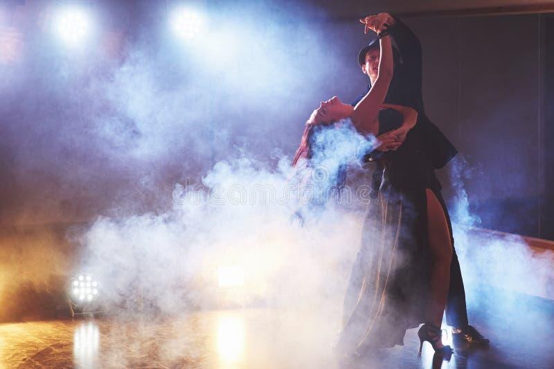Skickliga dansare som utför i det mörka rummet under konserten, tänder och röker Sinnliga par som utför ett konstnärligt royaltyfria foton