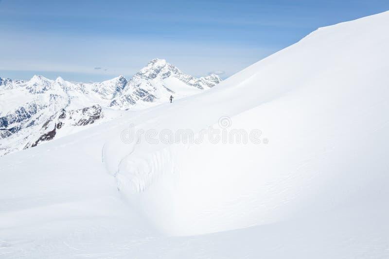 Skidåkare i avståndet över stor kornisch av windblown snö Ovanför honom är monteringen Sir Donald i glaciärnationalpark, Kanada royaltyfri foto