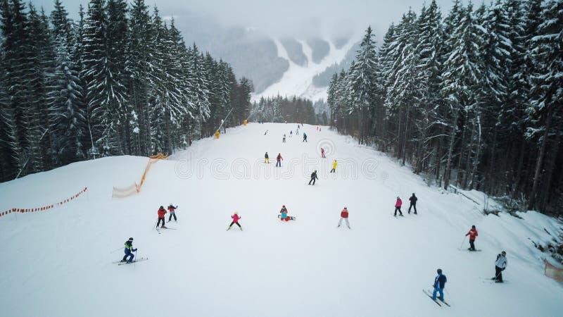 Skidåkare och snowboarders går ner lutningen i en skidasemesterort Bukovel, Ukraina royaltyfri fotografi