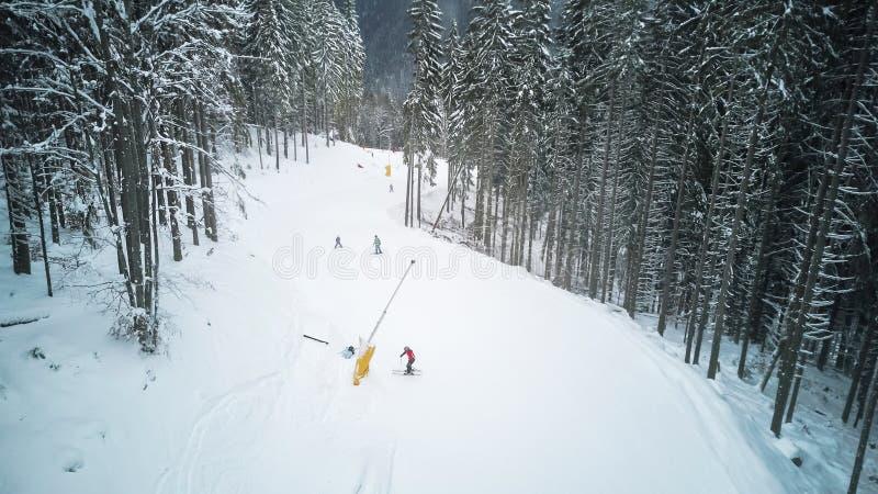 Skidåkare och snowboarders går ner lutningen i en skidasemesterort Bukovel, Ukraina fotografering för bildbyråer