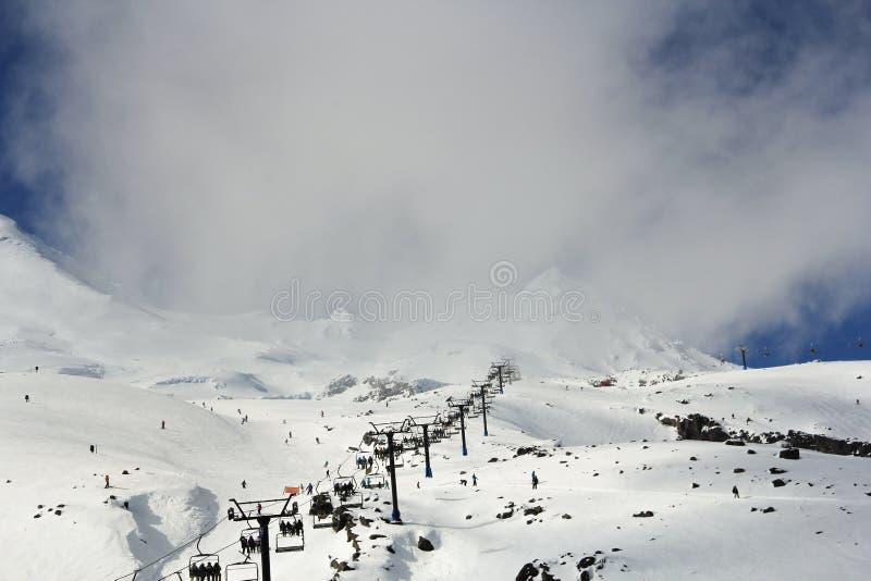 Skidåkare, snowboarders och turister som använder den kabelbilarna eller skidliften för att få till överkanten av en snö, täckte  arkivfoto