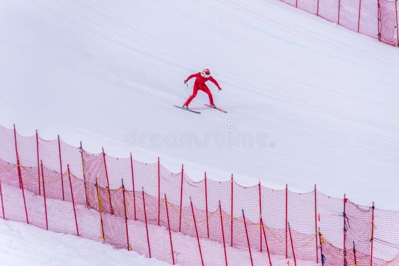 Skidåkare som försöker att sakta ner längst ner av stupet på hastighetsutmaningen och FIS-hastighet Ski World Cup Race på solmaxi arkivbild