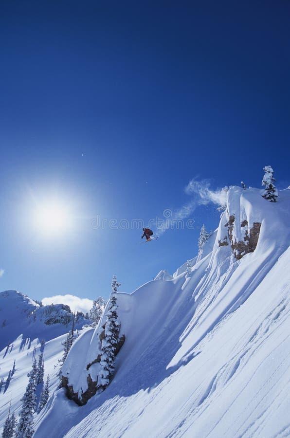 Skidåkarebanhoppning från berget royaltyfri fotografi