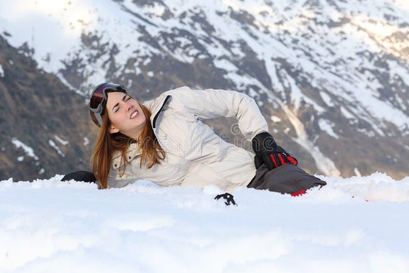 Skidåkarekvinnamen i snön arkivbild