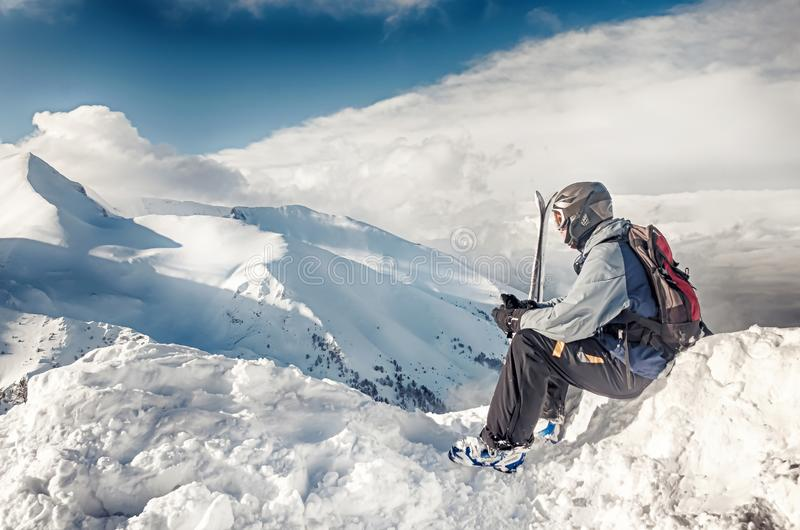 Skidåkaren sitter med skidar på stort vaggar på bergbakgrunden Bansko Bulgarien royaltyfria foton