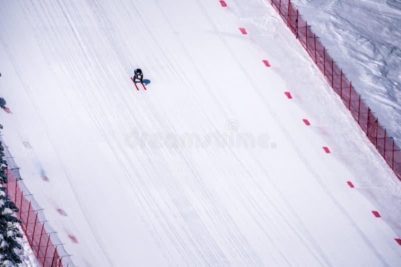 Skidåkaren som springer ner den branta hastighetsskidåkninglutningen på hastighetsutmaningen och FIS-hastighet Ski World Cup Race arkivbild