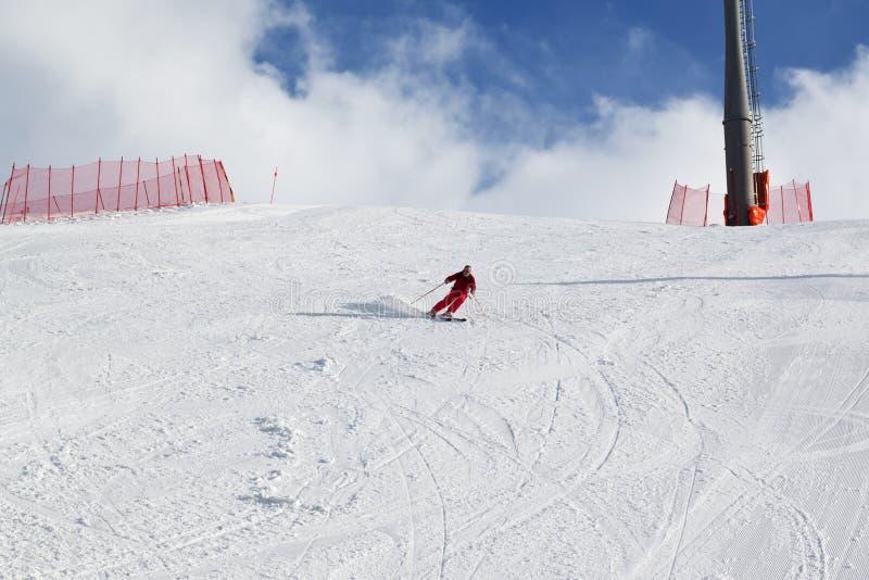 Skidåkaren stiger ned på snöig solljus skidar lutningen på den soliga vinterdagen royaltyfria bilder