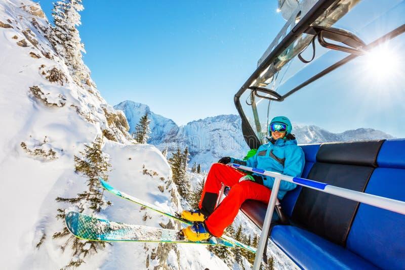 Skidåkaresammanträde på skidlift i höga berg under solig dag royaltyfri bild