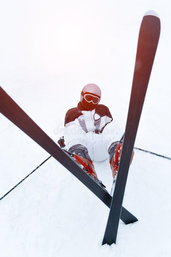 Skidåkaretonåringen som ligger i snön skidar på, semesterorten arkivbild