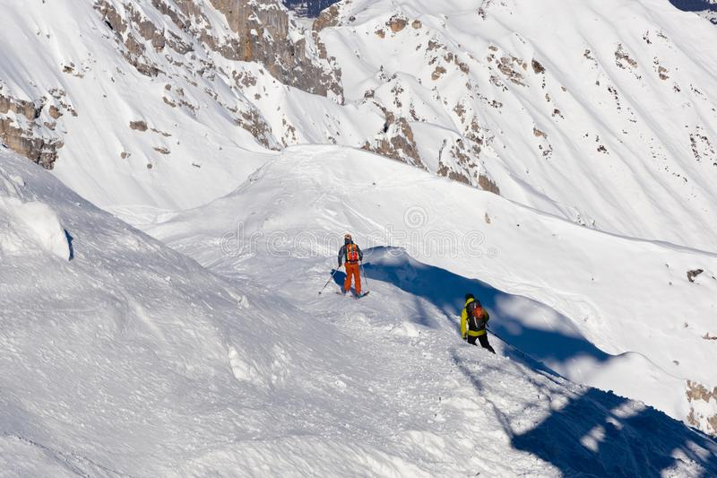 Skidåkning skidåkare, snålskjuts i ny pulversnö - mannen med skidar klättringar till överkanten arkivbild