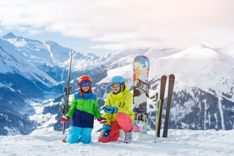 Skidåkning, vinter, snö, sol och gyckel - ungar, pojke och flicka som har gyckel i fjällängarna Barnskidåkning i bergen royaltyfria foton