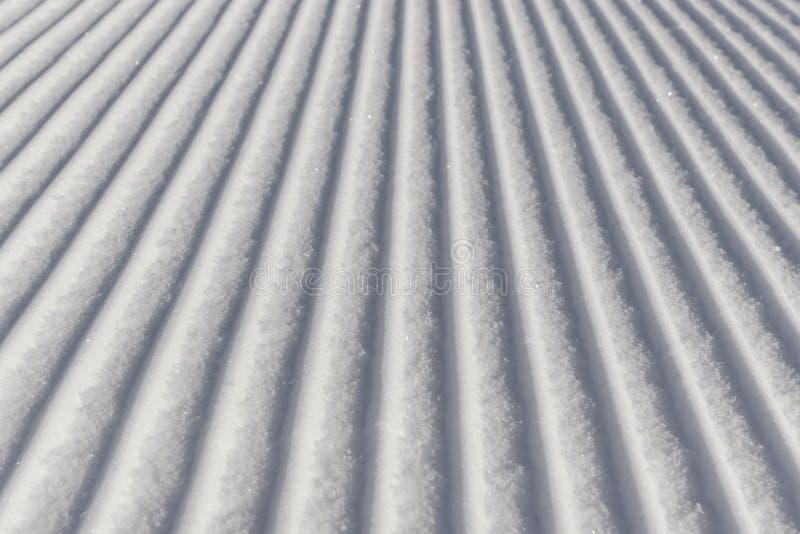 Skidåkningbakgrund - ny snö skidar på lutningen royaltyfria bilder