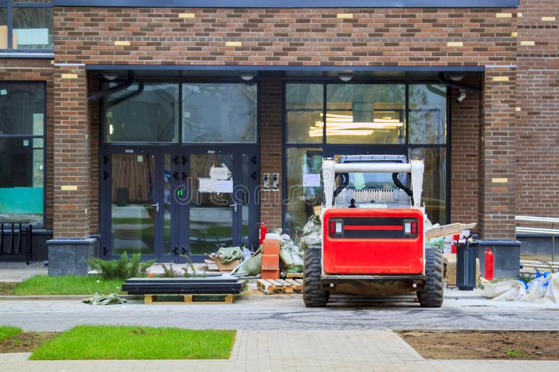 Skid loader stands in front of entrance to new multi-storey house and waits for garbage to be loaded into  bucket. Mini bulldozer stock photo