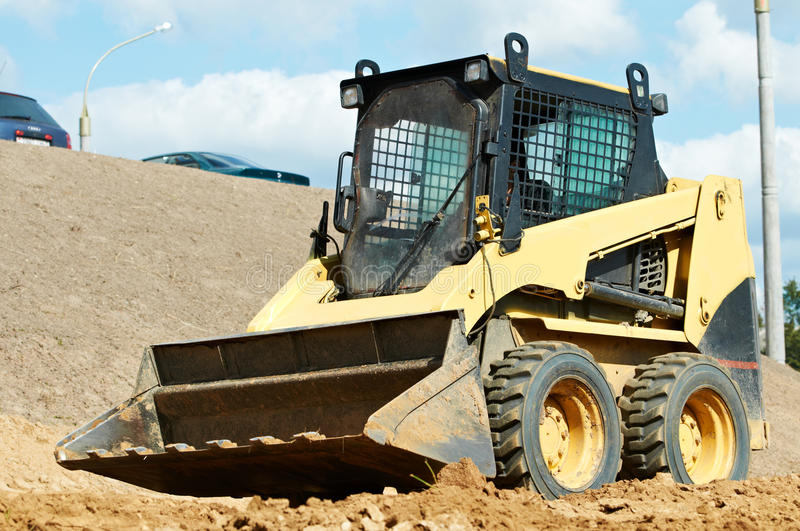 Skid steer loader at earth moving works royalty free stock photo