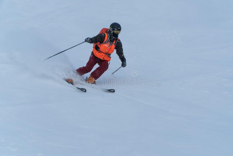Skida för skidåkare som är sluttande i höga berg under solig dag fotografering för bildbyråer