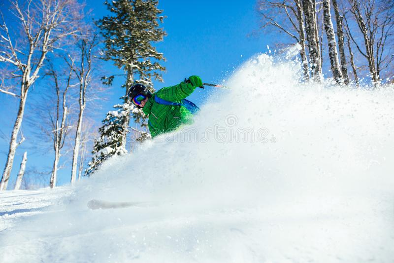 Skida för skidåkare som är sluttande under solig dag i höga berg fotografering för bildbyråer