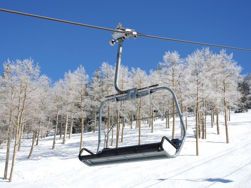 Skidar chairliften med is täckte asp- träd i bakgrunden arkivfoton