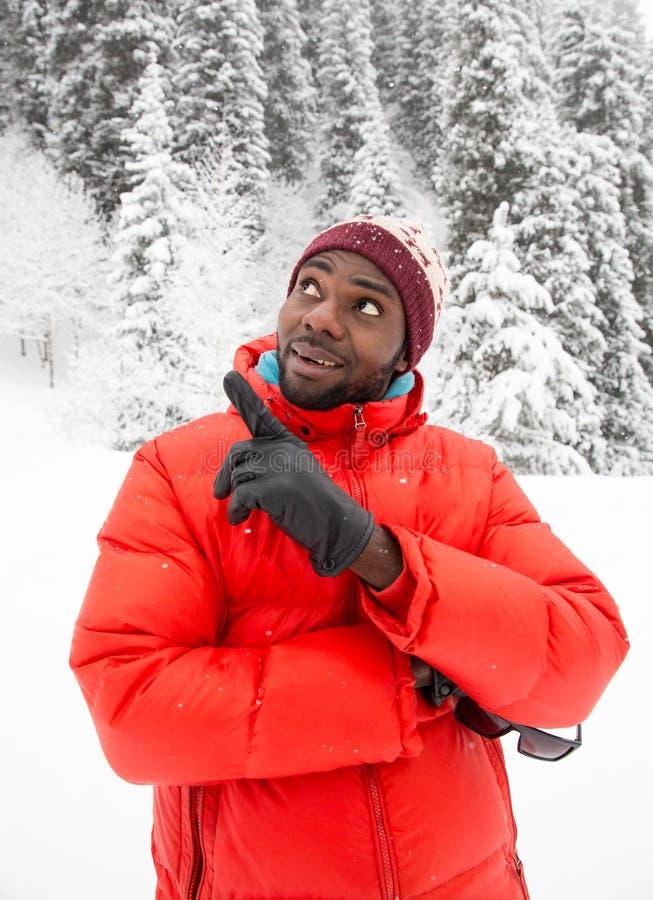Skidar den gladlynta svarta mannen för afrikanska amerikanen in dräkten i snöig vinter utomhus arkivbild