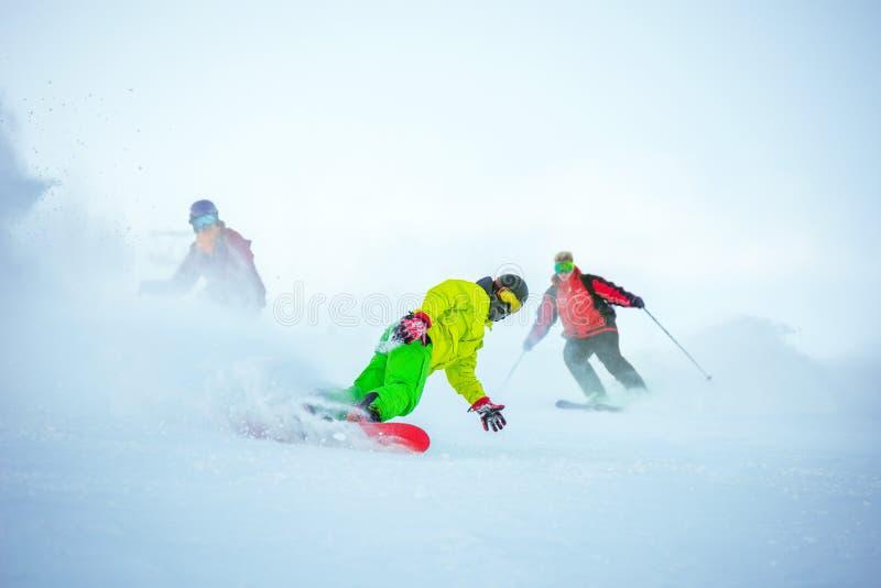 Skidar det sluttande begreppet med gruppen av snowboarders royaltyfri bild