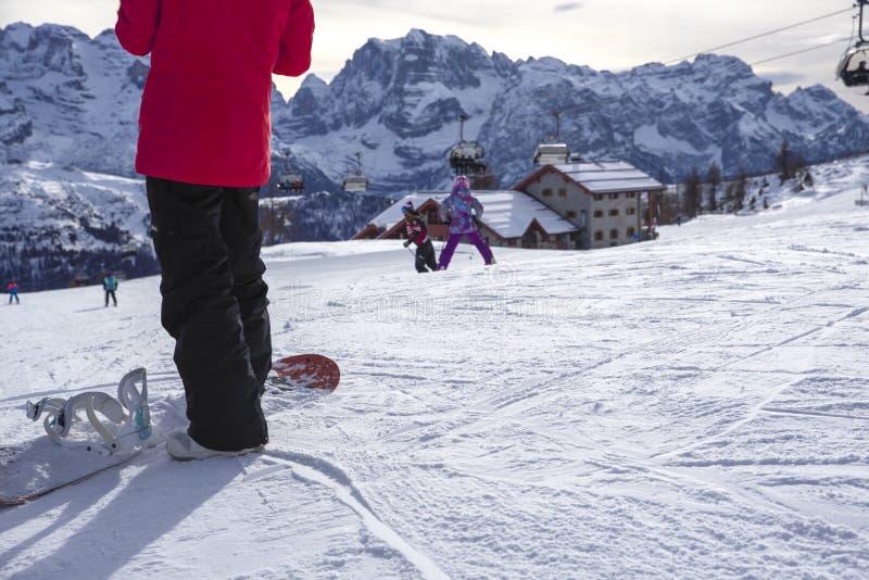 Skidar lutningar med snowboards i förgrunden arkivbild