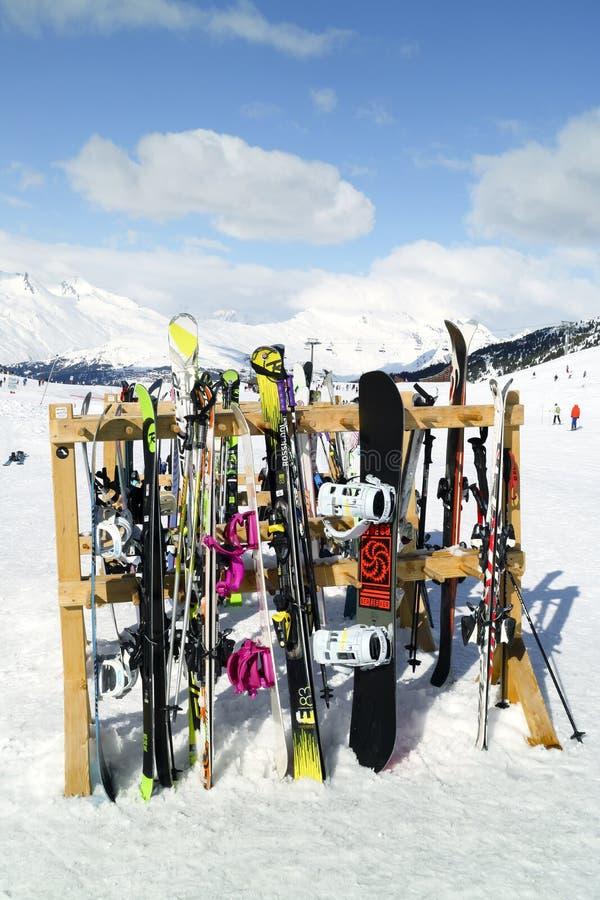 Skidar, och snowboards som står i snö nära apres, skidar stången royaltyfri bild
