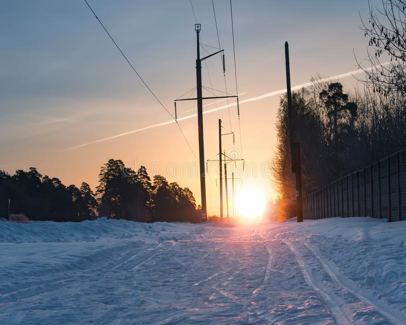Skidar sp?ret p? sn?yttersida mot stigningssolen arkivfoto