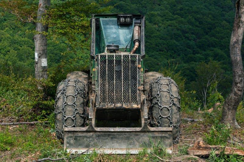 Skiddertraktor med tunga kedjor på gummihjul i frodig skog arkivbilder