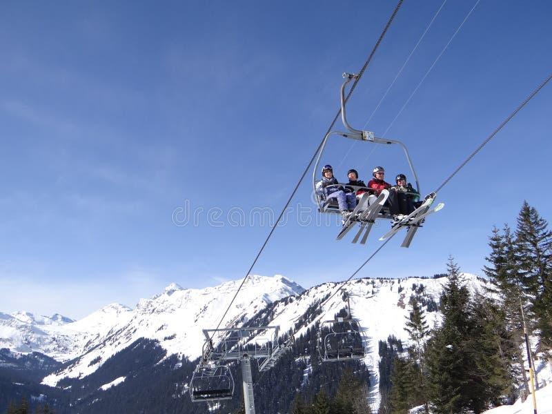 Skidlift bär ferieskidåkare upp berget royaltyfria bilder