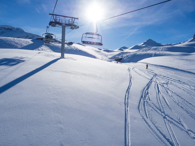 Skidlift med platser som går över berget och banorna från himlar och snowboards Frankrike Meribel, 2018 royaltyfria foton