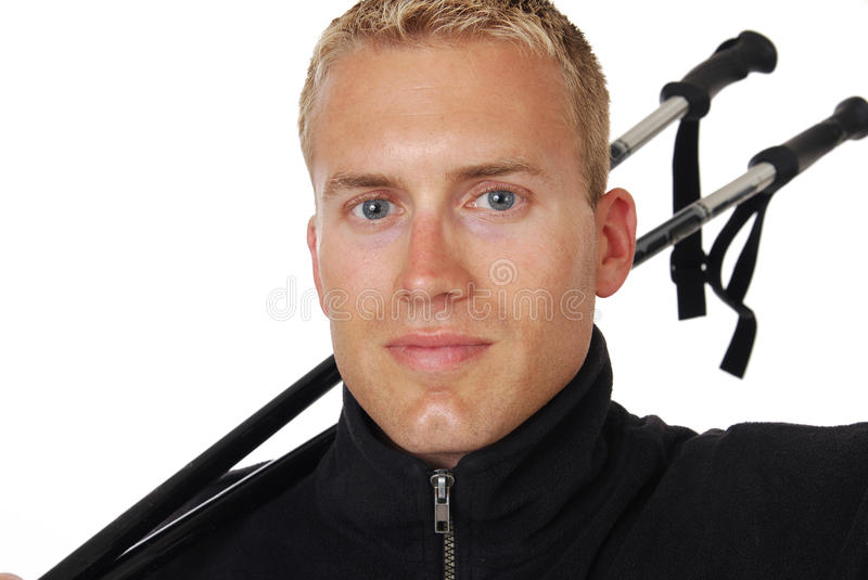 Skier. A handsome man with ski poles over his neck royalty free stock photography